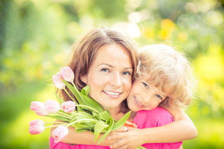 smiling mother: Mother and daughter with bouquet of flowers against green blurred background. Spring family holiday concept. Mothers day