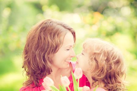 mamá: Madre e hija con el ramo de flores contra el fondo verde borrosa. Familia del resorte concepto de vacaciones. Dia de las Madres