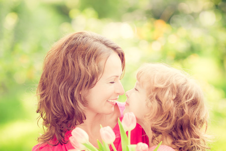 womens day: Mother and daughter with bouquet of flowers against green blurred background. Spring family holiday concept. Mothers day