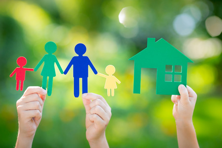 hand holding house: Paper house and family in hand against spring green background. Real estate business concept