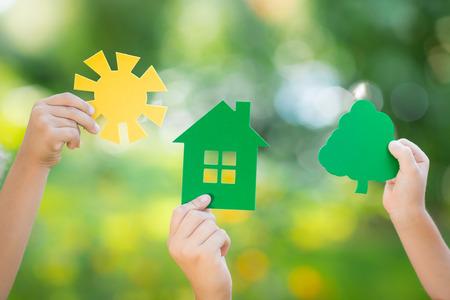 紙の家、木、春の緑に対して手で太陽は背景にぼやけています。生態学の概念