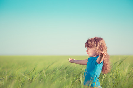 Happy child in spring field. Young girl relax outdoors. Freedom concept photo