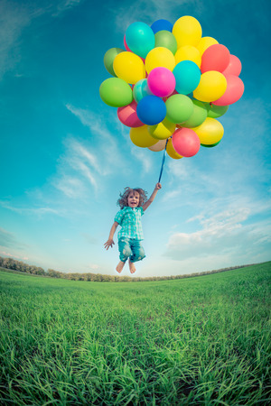 birthday background: Happy child jumping with colorful toy balloons outdoors. Smiling kid having fun in green spring field against blue sky background. Freedom concept