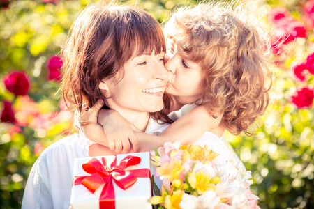 Happy woman and child with beautiful spring flowers against green background. Family holiday concept. Mothers day Stock Photo