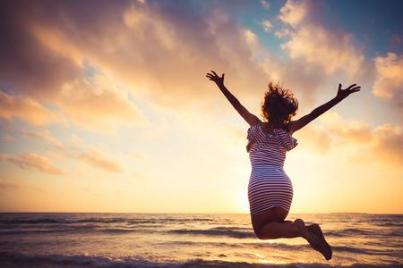 zbraně: Šťastná mladá žena skákat na pláži. Letní prázdniny koncept