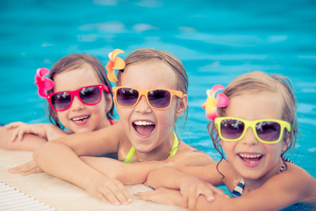 kinderen: Gelukkige kinderen in het zwembad. Grappige kinderen buiten spelen. Zomervakantie concept Stockfoto