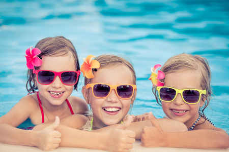 Happy children showing thumbs up in the swimming pool. Funny kids playing outdoors. Summer vacation concept