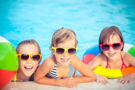 outdoor: Felices los niños en la piscina. Niños divertidos jugando al aire libre. Concepto de las vacaciones de verano