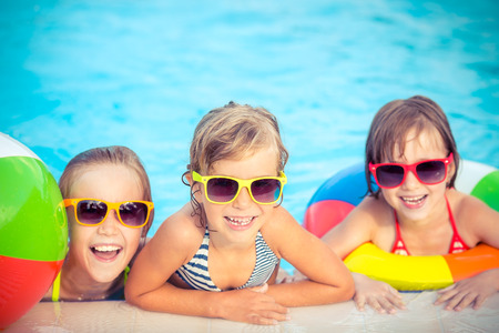 happy kids: Happy children in the swimming pool. Funny kids playing outdoors. Summer vacation concept