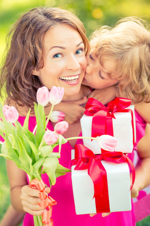 Mother and daughter with bouquet of flowers against green blurred background. Spring family holiday concept. Mothers day