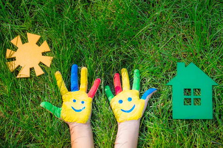 green smiley face: Smiley hands, paper house and sun on green grass. Children having fun in spring outdoors. Ecology concept Stock Photo