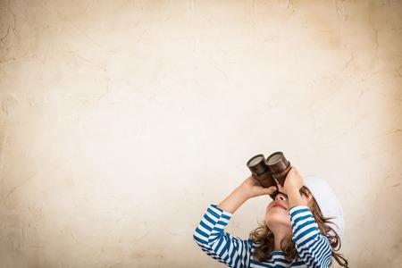 Bağbozumu deniz dürbün ile oynarken mutlu bir çocuk. Çocuk evde eğlenmek. Yaz deniz rüya ve hayal. Macera ve seyahat kavramı. Retro tonda görüntü