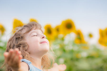 Happy child in spring sunflower field. Freedom concept