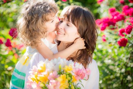 dia: Mujer y niño felices con hermosas flores de primavera contra el fondo verde. Concepto de vacaciones de la familia. Día de la Madre