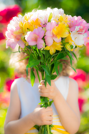 Beautiful flowers in hands against spring background. Family holiday concept. Mothers day Stock Photo