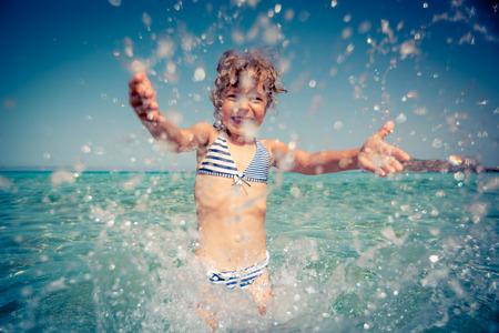 海で遊んで幸せな子。夏の休暇の概念