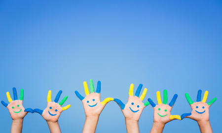 group of hands: Happy people with smiley on hands against blue summer sky background Stock Photo