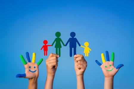 Gelukkig gezin. Kinderen met een smiley op handen tegen de blauwe hemel zomer achtergrond