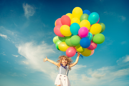 vintage children: Happy child jumping with colorful toy balloons outdoors. Smiling kid having fun in green spring field against blue sky background. Freedom concept