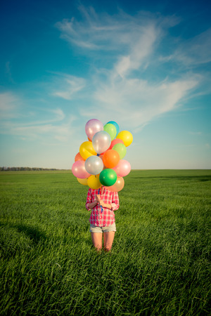 Happy girl playing with colorful toy balloons outdoors.  photo