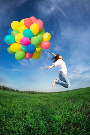 Happy young woman jumping with colorful balloons in green field against blue sky background.