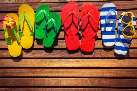 Multicolor flip-flops on wooden background. Summer family vacation concept Archivio Fotografico