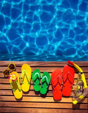 青い水の背景に木製の板で多色フリップフ ロップ。夏の家族旅行のコンセプト 写真素材