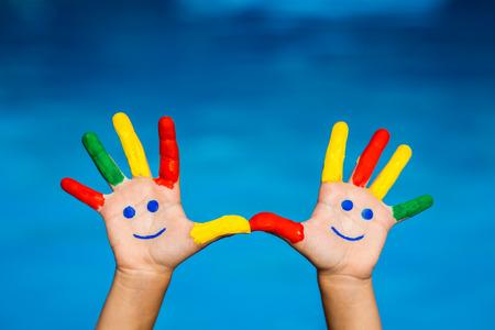 Smiley руками на синем фоне воды. Летние каникулы концепция Фото со стока