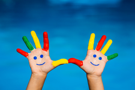 Smiley handen tegen blauwe water achtergrond. Zomervakantie concept Stockfoto