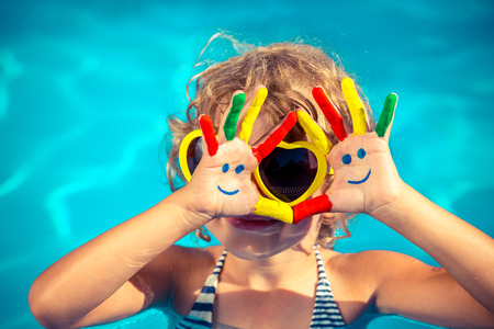 smiley: Funny child with drawing smiley on hands in swimming pool. Summer vacation concept