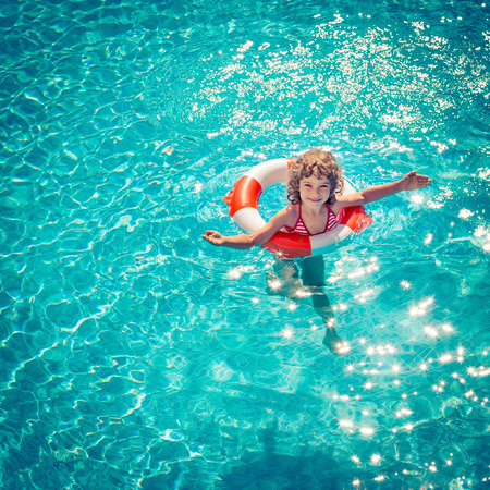 baby swimming: Happy child playing in swimming pool. Summer vacation concept. Top view portrait Stock Photo
