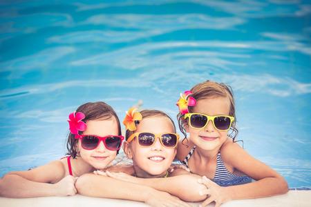 jugando: Felices los ni�os en la piscina. Ni�os divertidos jugando al aire libre. Concepto de las vacaciones de verano