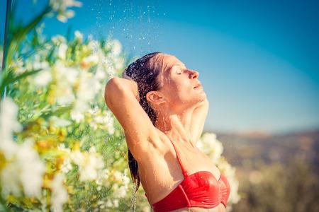 mujer bañandose: Mujer joven que toma la ducha al aire libre. Las vacaciones de verano y el concepto de estilo de vida saludable Foto de archivo