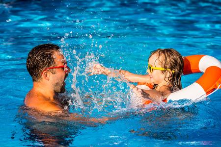 nadando: El ni�o feliz y padre jugando en la piscina. Concepto de las vacaciones de verano