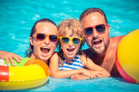 persona alegre: Familia feliz jugando en la piscina. Concepto de las vacaciones de verano Foto de archivo