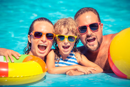 splash pool: Happy family playing in swimming pool. Summer vacation concept