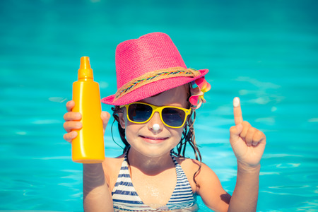 sun lotion: Happy child holding sunscreen lotion in hand. Summer vacations concept