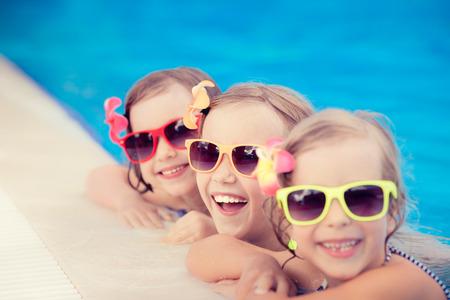 anteojos de sol: Felices los niños en la piscina. Niños divertidos jugando al aire libre. Concepto de las vacaciones de verano