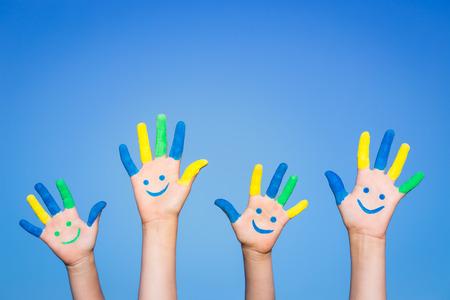 Gelukkige familie met smiley op handen tegen de blauwe hemel zomer achtergrond Stockfoto