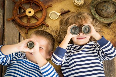 Crianças felizes brincando com coisas náuticas. Crianças se divertindo em casa. Conceito de viagens e aventura. Retrato de vista de alto ângulo incomum Foto de archivo