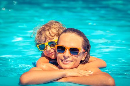 madre: Niño feliz y una mujer jugando en la piscina. Concepto de las vacaciones de verano Foto de archivo