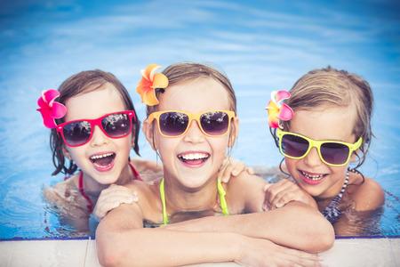 ni�os riendo: Felices los ni�os en la piscina. Ni�os divertidos jugando al aire libre. Concepto de las vacaciones de verano