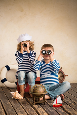 vintage look: Children playing with vintage nautical things. Kids having fun at home. Travel and adventure concept. Retro toned image