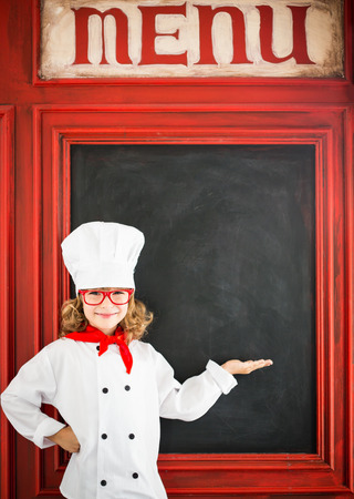 Child chef cook against blackboard blank menu with drawing healthy food. Restaurant business concept Stock Photo