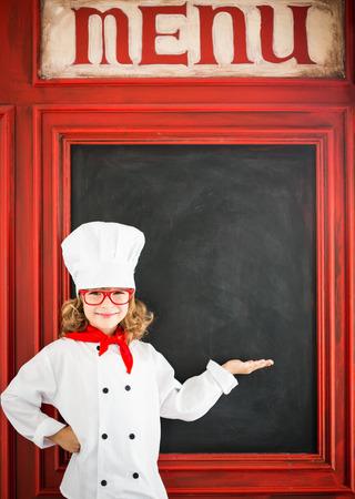 Kinderküchenchef gegen Tafel leere Menü mit Zeichnung gesundes Essen. Restaurant Geschäftskonzept Standard-Bild - 38974425