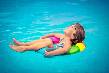 niñas jugando: Niño feliz que juega en la piscina. Concepto de las vacaciones de verano
