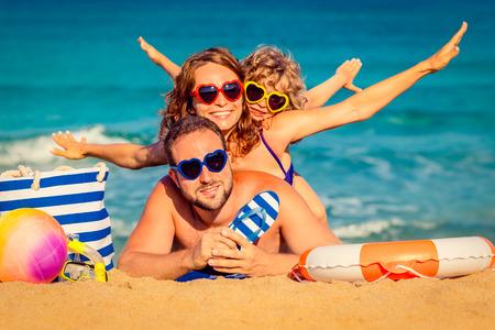 家庭: 幸福的家庭在海邊玩耍。暑假的概念