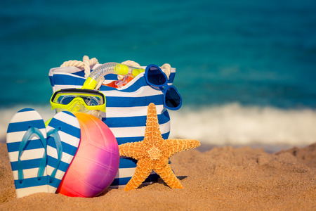 Striped bag, starfish and flip-flops on the beach. Summer vacation concept Stock Photo