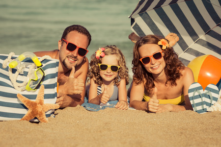 Happy family lying on the beach. People showing thumbs up. Summer vacation concept. Retro toned image Stock Photo