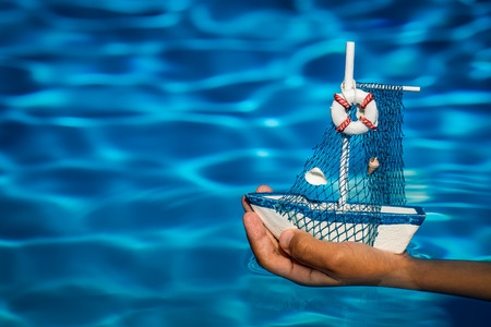 Summer vacation concept. Toy sailing boat in hands on the water background photo